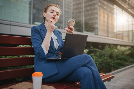 Worker applying lipstick in the street and working on PC at the same time. Businesswoman doing multiple tasks. Multitasking business person. Stock Photo