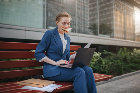 Worker eating and working with documents on the laptop at the same time. Businesswoman doing multiple tasks. Multitasking business person. Stock Photo