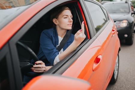 Una donna sente lo stress sulla strada. Mostra il fatto nella finestra. Big Traffic Jam. La donna d'affari è in ritardo per il lavoro Archivio Fotografico