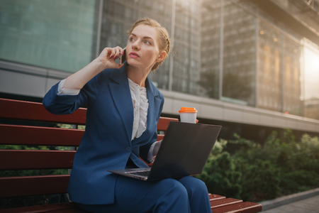 Young woman sitting outdoors and using laptop. Businesswoman working. Holding cup of coffee. and speaking on the phone at the same time