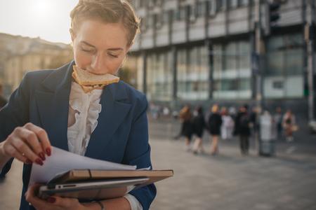 Mulher ocupada está com pressa, ela não tem tempo, ela vai comer lanche em movimento. Trabalhador comendo, tomando café, falando ao telefone, ao mesmo tempo. Empresária, fazendo várias tarefas. Pessoa de negócios multitarefa.