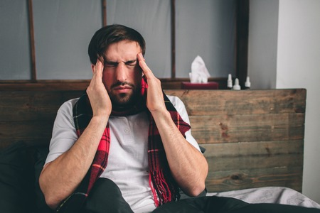 picture from a young man with handkerchief. Sick guy lies in bed and has runny nose. man makes a cure for the common cold. Model male has a high temperature, headache, migraine