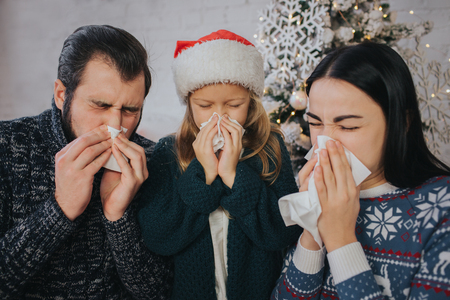 Family is sick at Christmas They have handkerchief. Sick people have runny nose. Merry Christamas and Happy New Year
