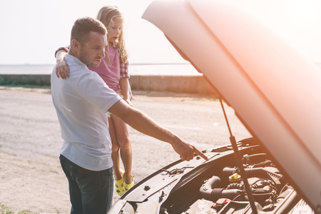 Przystojny ojciec uczy swoją córkę w wieku szkolnym, jak wymieniać olej silnikowy lub naprawiać rodzinny samochód.