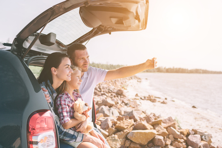 Happy family on a road trip in their car. Dad, mom and daughter are traveling by the sea or the ocean or the river. Summer ride by automobile Standard-Bild