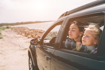 Famiglia felice in viaggio in macchina. Papà, mamma e figlia stanno viaggiando al mare, all'oceano o al fiume. Giro estivo in automobile. Archivio Fotografico