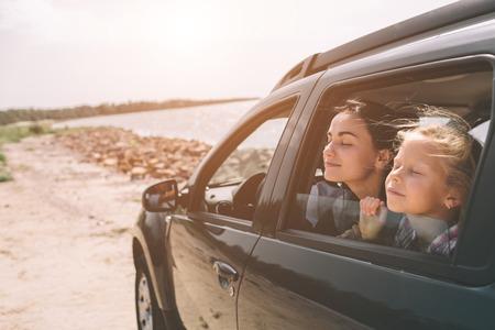 Famille heureuse lors d'un voyage sur la route dans leur voiture. Papa, maman et fille voyagent au bord de la mer, de l'océan ou de la rivière. Balade estivale en automobile. Banque d'images