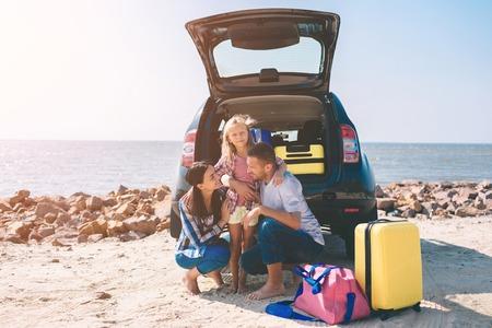 Jeune couple debout près du coffre de voiture ouvert avec valises et sacs. Papa, maman et fille voyagent au bord de la mer, de l'océan ou de la rivière. Balade estivale en automobile