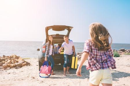 Pareja joven de pie cerca del maletero del coche abierto con maletas y bolsos. Papá, mamá e hija viajan por el mar o el océano o el río. Paseo de verano en automóvil Foto de archivo