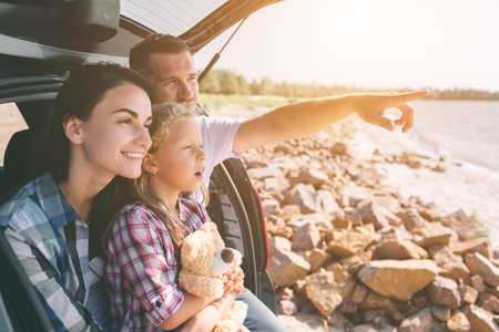 Happy family on a road trip in their car. Dad, mom and daughter are traveling by the sea or the ocean or the river. Summer ride by automobile 版權商用圖片
