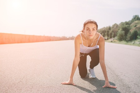 Young woman athlete at starting position ready to start a race. Female sprinter ready for sports exercise on racetrack with sun flare