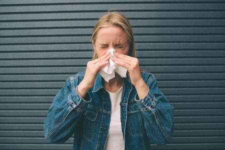 picture from a young woman with handkerchief. Sick female model has runny nose. Stock Photo