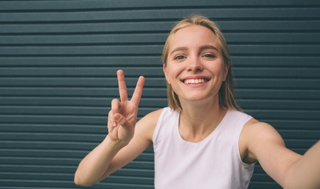 Beautiful young woman making self-portrait on a smartphone on a wall background.