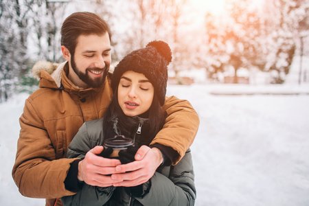 Happy Young Couple in Winter . Family Outdoors. man and woman looking upwards and laughing. Love, fun, season and people - walking in winter park. Its snowing, theyre hugging. They drink coffee.