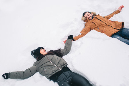 Happy Young Couple in Winter . Family Outdoors. man and woman looking upwards and laughing. Love, fun, season and people - walking in winter park. Lying in fresh snow, making snow angels having fun