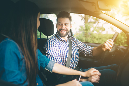 Condução cuidadosa. Bela jovem casal sentado nos bancos do passageiro da frente e sorrindo enquanto homem bonito dirigindo um carro
