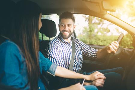 Vorsichtiges Fahren. Schöne junge Paare, die auf den Beifahrersitzen sitzen und während Autofahren des gutaussehenden Mannes lächeln