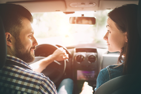 조심성있는 운전. 아름 다운 젊은 부부 앞 좌석에 앉아 하 고 웃 고 잘 생긴 남자 차를 운전하는 동안 웃 고