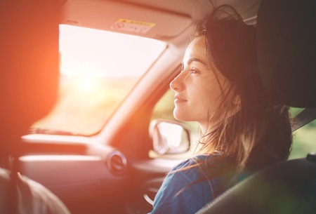 Beautiful woman smiling while sitting on the front passenger seats in the car Foto de archivo