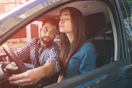 Prueba de manejo. Mujer seria joven que conduce el coche sintiéndose inexperta, que parece nerviosa en el tráfico en busca de información para tomar decisiones apropiadas. El hombre es instructor, controla y verifica.