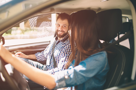 Careful driving. Beautiful young couple sitting on the front passenger seats and smiling while woman driving a car Banco de Imagens
