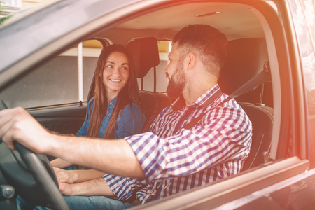Careful driving. Beautiful young couple sitting on the front passenger seats and smiling while handsome man driving a car Stock Photo