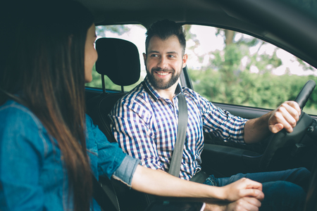 Careful driving. Beautiful young couple sitting on the front passenger seats and smiling while handsome man driving a car 版權商用圖片
