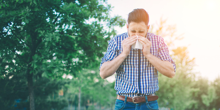 picture from a young man with handkerchief. Sick guy has runny nose. Stock Photo