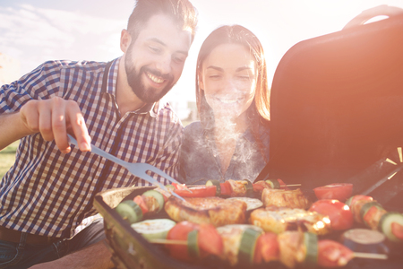 Friends making barbecue and having lunch in the nature. Couple having fun while eating and drinking at a pic-nic - Happy people at bbq party.