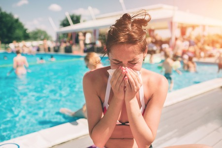 picture from a Beautiful women in bikini with handkerchief. Sick female model has runny nose. girl makes a cure for the common cold. She is sick in the summer on vacation. Stockfoto