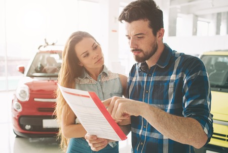 Beautiful young couple standing at the dealership choosing the car to buy Stock Photo