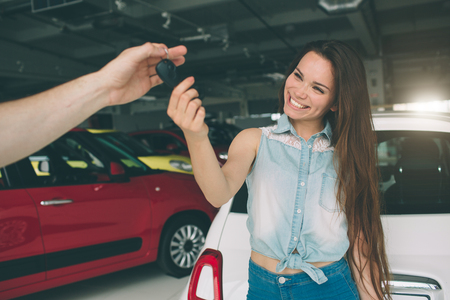 Beautiful young woman is holding a key in car dealership. Auto business, car sale, - happy female model in auto show or salon Standard-Bild