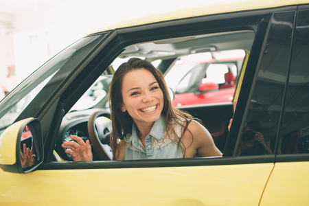 Beautiful young woman buying a car at dealership. Female model sitting in the car interior Stockfoto