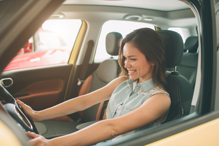beautiful young woman buying a car at dealership. Female model sitting Sits in the car interior Stock Photo