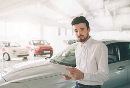 friendly vehicle salesman presenting new cars at showroom. Photo of young male consultant showing new car in auto show. Concept for car rental.