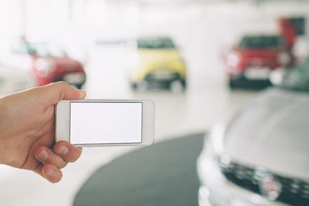 携帯電話の白い画面を使用して手。車の販売、市場の場所。車のショールーム