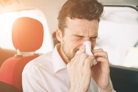 de um jovem com lenço. O cara doente tem nariz escorrendo. homem faz uma cura para o resfriado comum no carro Foto de archivo