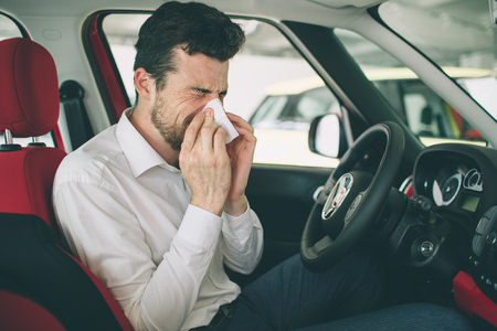 from a young man with handkerchief. Sick guy has runny nose. man makes a cure for the common cold in the car Foto de archivo