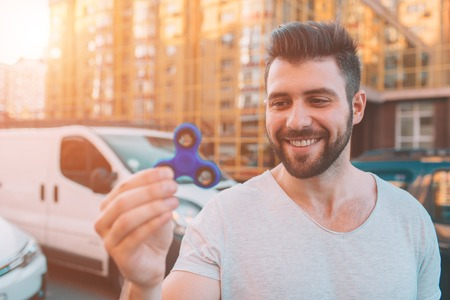 Young man holding and playing with fidget spinner