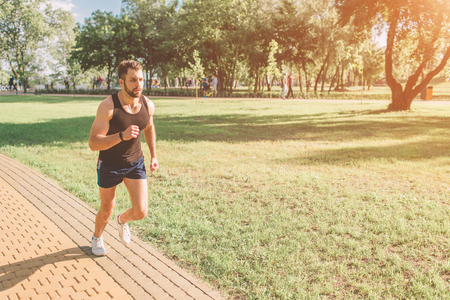 Athletic young man running in the nature. Healthy lifestyle. Bearded black haired sportsman is running on road - sunset back lit