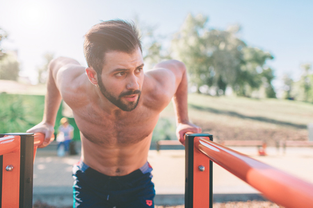 A portrait of a focused muscular bearded man in black workout clothes doing dips on parallel bars . Mans fitness with blue sky in the background and open space around him. Sports and crossfit. Imagens