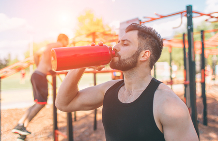 Man holding iron bottle and drinking water. Young handsome well formed sporty man resting after training outdoors. Male fitness model training workout. Banco de Imagens