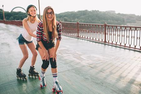 Twee slanke en sexy jonge vrouwen en rolschaatsen. Eén vrouw heeft een inline-skates en de andere heeft een quad-skates. Meisjes rijden in de stralen van de zon