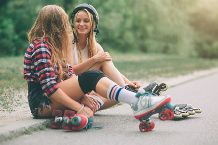 """Duas mulheres novas magros e """"sexy"""" e patins de rolo. Uma fêmea tem patins inline e a outra tem patins quad. As meninas andam nos raios do sol."""