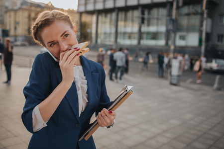Busy woman is in a hurry, she does not have time, she is going to eat snack on the go. Worker eating, drinking coffee, talking on the phone, at the same time. Businesswoman doing multiple tasks. Multitasking business person.