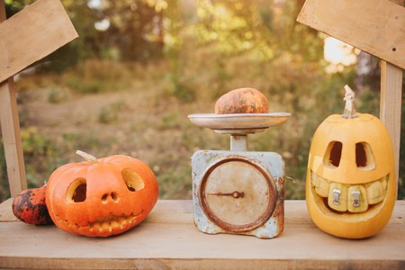 Ghost pumpkins on Halloween. ead Jack on an autumn background. Holiday outdoor decorations Stock Photo