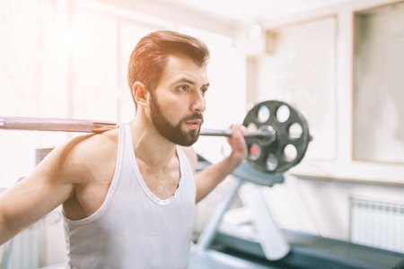 Gespierde bebaarde man tijdens training in de sportschool. Bodybuilder die gewichtheffen doet. Sluit omhoog van jonge atletische vrouwelijke modeltreinen op het geschiktheidscentrum. Stockfoto