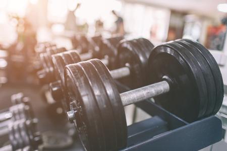 Conjunto de haltere preto. Feche acima de muitos dumbbells no fitness center do esporte. As fileiras na ginástica com contraste do hign e o tom da cor ostentam e conceito da saúde. Foto de archivo - 93442115