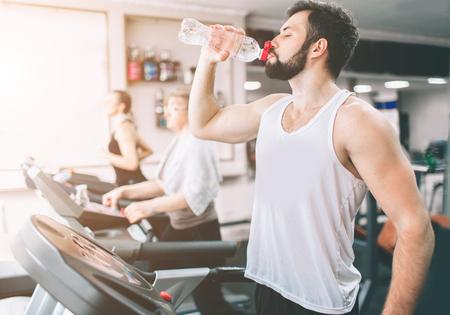 Jonge man in sportkleding draait op loopband en drinkwater in de sportschool. Gespierde bebaarde atleet tijdens training. Sluit omhoog van jonge atletische vrouwelijke modeltreinen op het binnengeschiktheidscentrum.