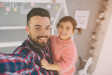 Cute little daughter and her handsome young dad are playing together in childs room. Daddy and child spend time together while sitting on the floor in bedroom.